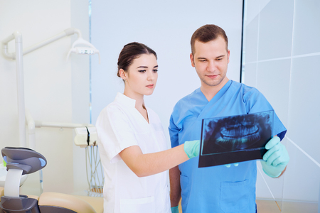 Two doctors dentist looking at an x-ray in office. Stock Photo