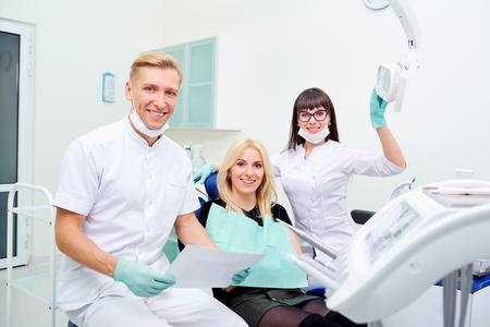 De patiënt, tandarts en assistent in kantoor van een tandheelkundige kliniek. Stockfoto