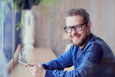 A freelance hipster man with  tablet in his hand works cafe by the window. Stock Photo