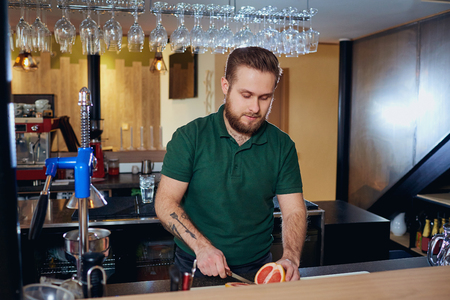 cleaning service: The barman prepares fresh juice at bar. Barista cut citrus on  table in  restaurant. Stock Photo