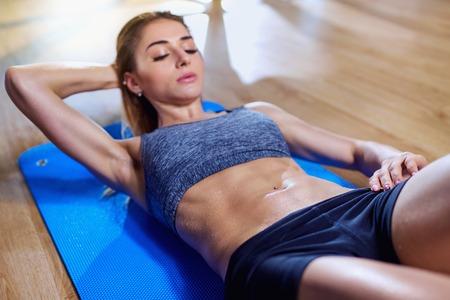 Meisje op vloer die oefeningen op de maag in de gymnastiek doet. Nat lichaam. Stockfoto