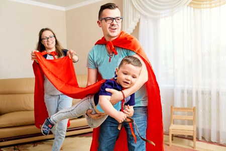 Een familie gekleed in superhelden kostuums speelt de kamer. Stockfoto - 76439576
