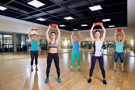 synchronously: Group training of women in the gym.
