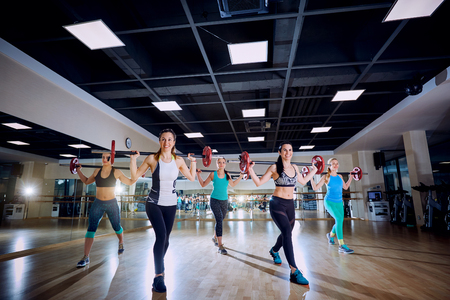 synchronously: Group training. Girls doing exercises with a bar in the gym. Stock Photo