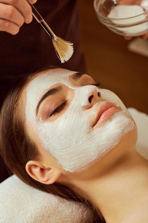 Op het gezicht van de vrouw zorgt de schoonheidsspecialist voor een masker in de spa.