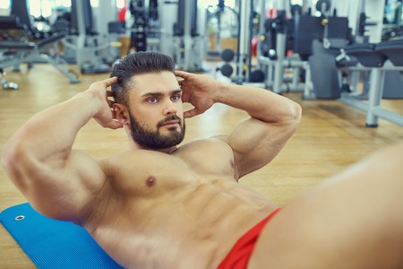 laying abs exercise: bodybuilder with a beard does abs exercise on the floor in the gym.