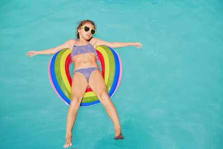 A teenage girl in a circle ring in the water at the pool.