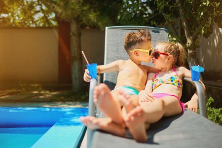 Verliefde paar kind kinderen op een ligstoel bij het zwembad in de zomer. Concept Dag Valentijnsdag. Stockfoto