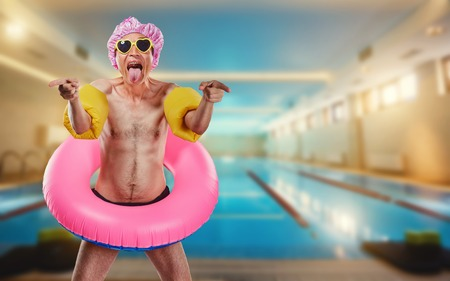 Humor. A thin man in a shower cap and a circle around the pool.