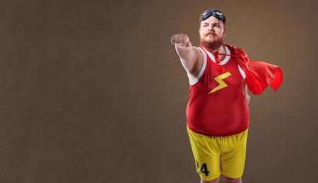 スーパー ヒーローの衣装でデブの面白い男。 写真素材