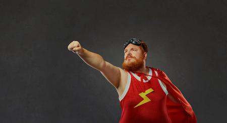Fat funny man in a superhero costume.Concept success. Standard-Bild