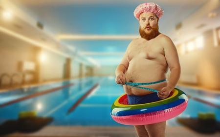プールの膨脹可能なサークルでデブの面白い男。
