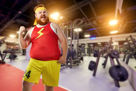 Thick fat funny man winner smiles in sports clothes in the gym. Stock Photo