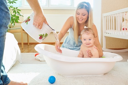 Parent bathes the baby child in the bathroom in the room.