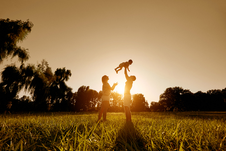 Happy family playing with a child at sunset in the park. Dad throws his child up in nature. Stock Photo