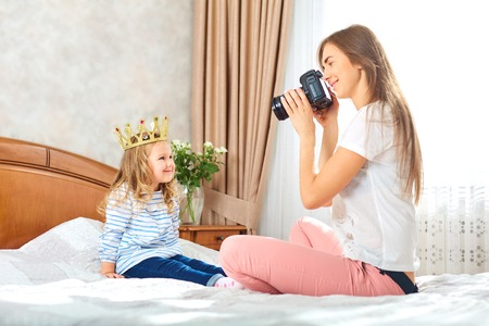 Mom takes pictures of her child in a room by the window. Mothers Day.