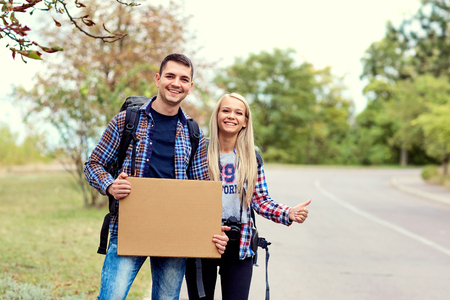 A pair of hitchhikers stand on the road. Фото со стока - 87750566
