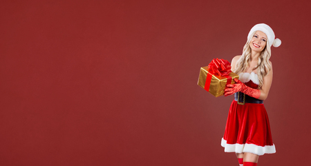 Cristmas: Girl in santa costume with a gift box in hands on a red Christmas background. Place for text. Stock Photo