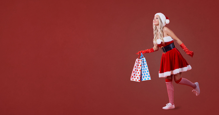 A Girl In Santa Claus Costume Is Running With Packages Of Gifts ...