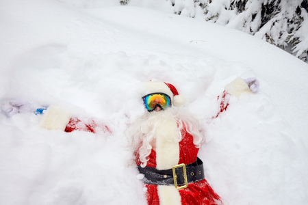 Santa Claus lies on the snow in winter for Christmas.