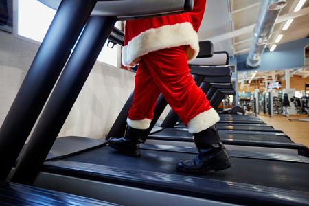 Santa Claus in de sportschool doen oefeningen. Stockfoto
