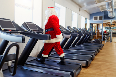 Santa Claus in the gym doing exercises. 스톡 콘텐츠