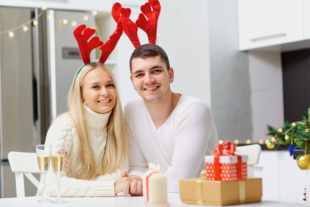 Couple in reindeer horns gives a Christmas present in the room.