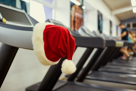 Santas hat in the gym. Concept of sports on Christmas and New Year. Stock Photo
