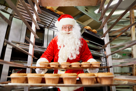 Santa Claus baker with a tray of cupcakes in his hands during Christmas. Standard-Bild