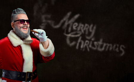 Santa Claus with a hairstyle and a cigar launches a smoke with the text of Merry Christmas. Stock Photo