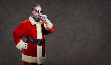 Santa Claus with a fashion hairdress smokes a cigar on the background of copyspace.