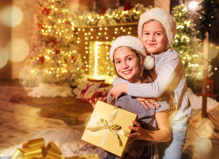 Two children with gifts in a room with a decor on Christmas.