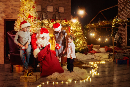 Santa Claus gives presents to children near the fireplace on Christmas Day. Stock Photo