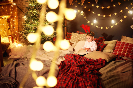 A child little boy is reading a book in the Christmas room.