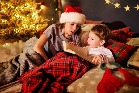 A children is reading a book in the Christmas room. Stock Photo