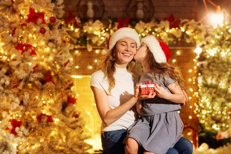 Mother and daughter in Santa hats give presents in a room with a fireplace and a Christmas tree on Christmas. Stock Photo