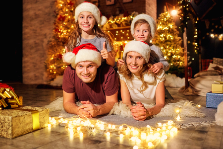 Happy family in a room with a Christmas tree on Christmas Day. Stock Photo