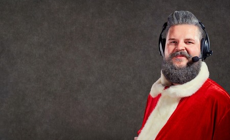 Santa Claus in a headset call center operator on a copyspace background. Stock Photo