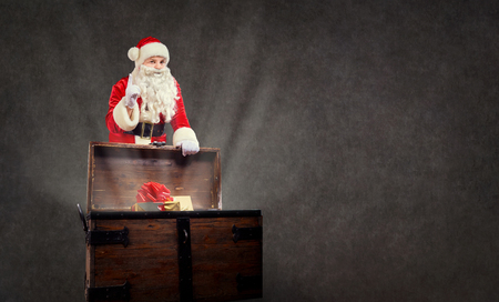 Santa Claus with a chest of gift presents on a copyspace background.
