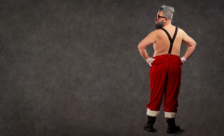 Santa Claus is a modern hairstyle with a naked body behind the back of the copyspace. Stock Photo