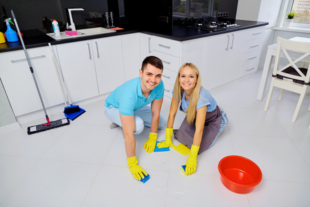 Young family couple doing cleaning in the kitchen.