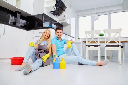 Young family couple doing cleaning in the house. Home cleaning.