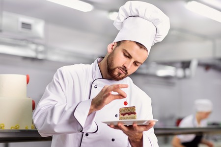 The confectioner is preparing a cake in the kitchen of the pastry shop.