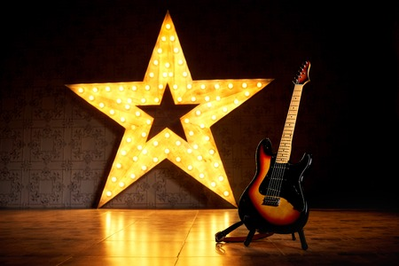 An electric guitar on the background of a large electric star with luminous bulbs. Stock Photo