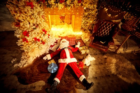 Santa Claus is lying drunk tired on the floor by the fireplace after Christmas.