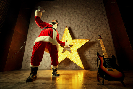 Happy Santa sings into the microphone against the backdrop of a big electric star on Christmas Day.