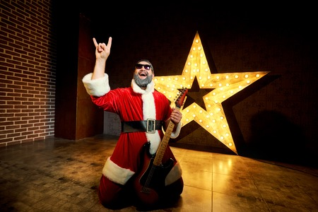 Happy Santa with a guitar is dancing against the background of a big electric star in Christmas. Stock Photo