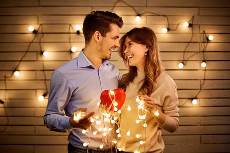 St. Valentines Day. A loving couple with a heart in garland light. Stock Photo