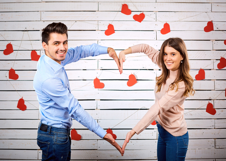 Young couple on Valentines Day. A loving couple makes a symbol of the heart with their hands.