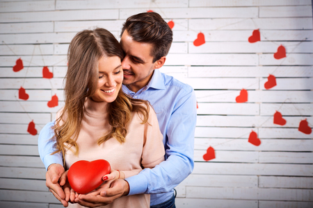 Young couple on Valentines Day. A loving couple hugs with a heart in their hands. Stock Photo
